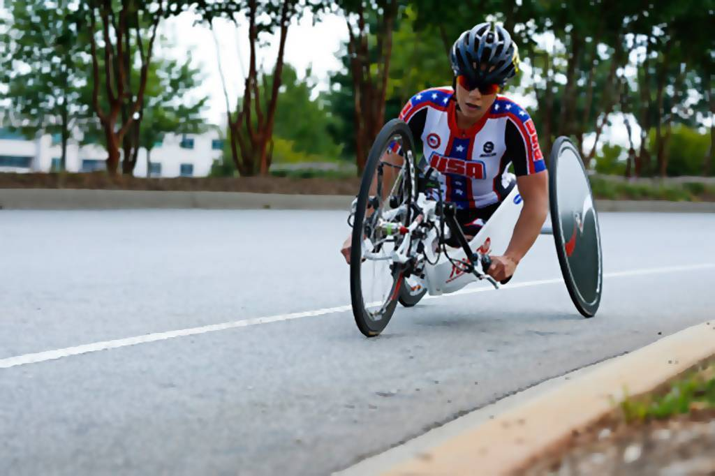 Photo of Oksana competing in para-cycling in her Team USA jersey.